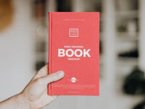 Free Holding Book Mockup (PSD)
